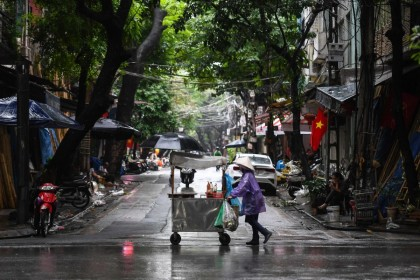 A street vendor pushes her cart in the rain in Hanoi, 15 October 2020. (Nhac Nguyen/AFP)