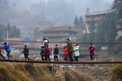 People on a bridge in a village in a Miao minority autonomous region in Liuzhou city, Guangxi, 30 January 2021. (Xinhua)