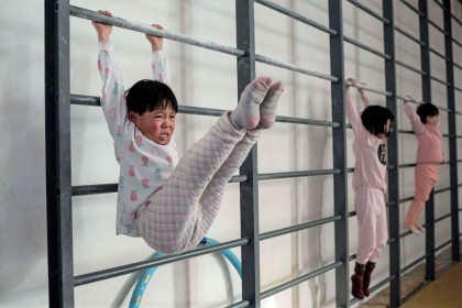 In this picture taken on 11 January 2021, young gymnasts train at the Li Xiaoshuang Gymnastics School in Xiantao, Hubei province, China. (Nicolas Asfouri/AFP)